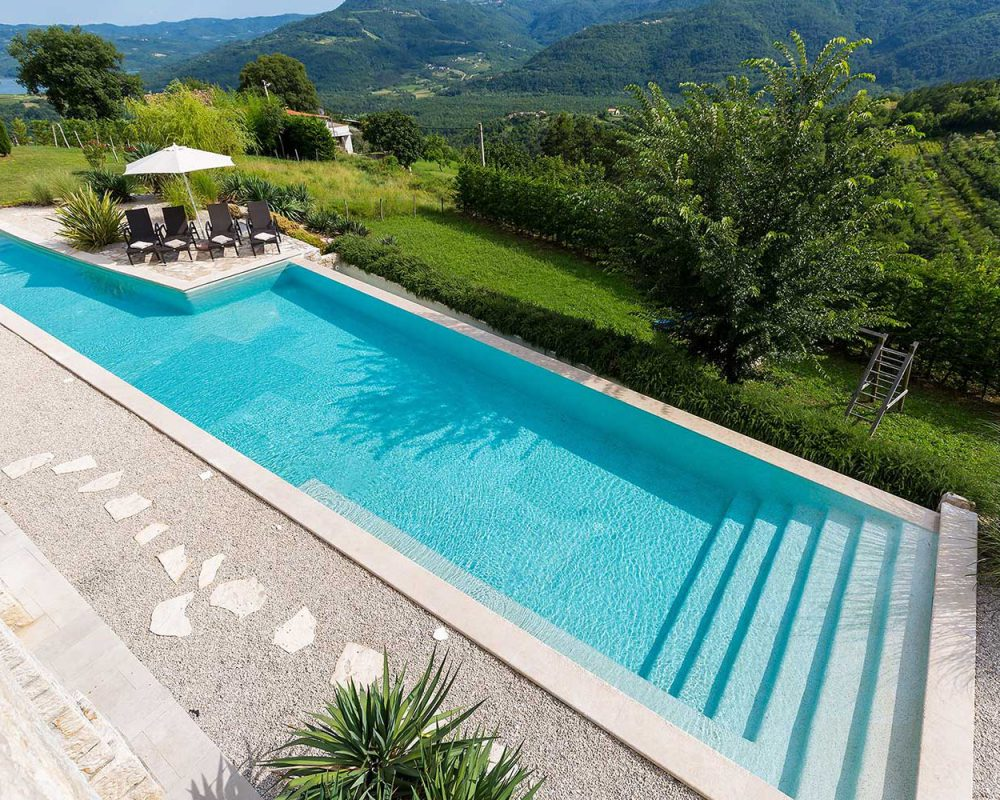 Der 80m² große Infinity Pool der Villa Kirin in Istrien hat zwei gegenüberliegende Treppen, die ins erfrischende Wasser führen.