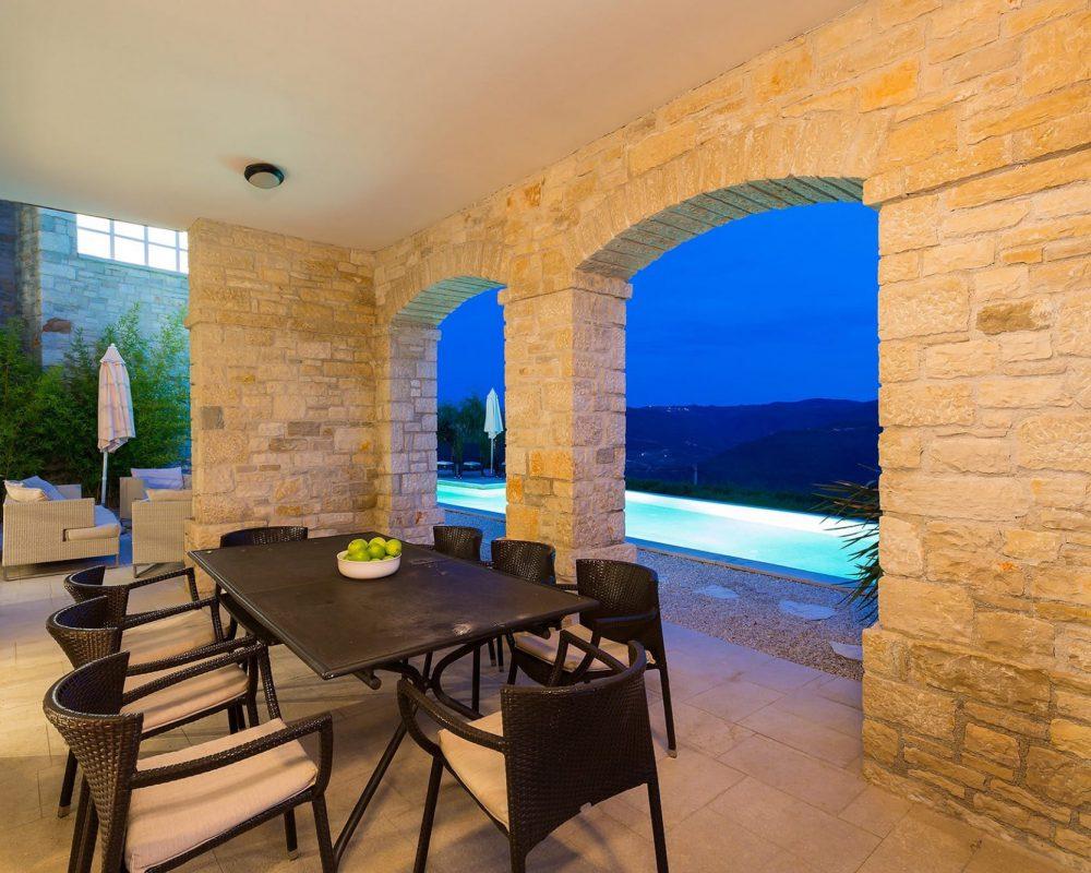 Im Außenbereich befindet sich eine überdachte Terrasse, gegenüber des Swimmingpools. In der Mitte steht ein Esstisch mit Acht Stühlen.
