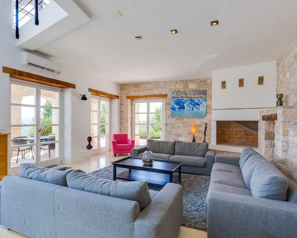 Die elegente Sitzlandschaft der Villa Kirin, besteht aus drei komfortbablen Couchs. Ein offener Kamin macht das Zimmer perfekt.