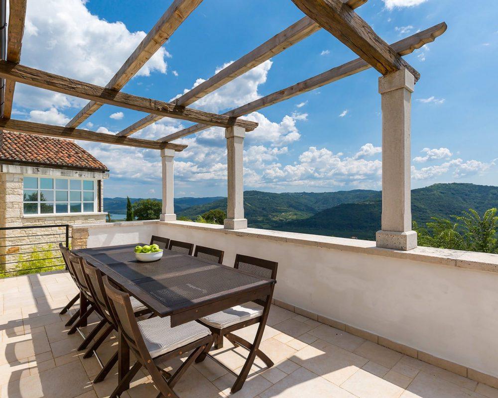 In der Mitte der Dachterrasse steht ein schicker Esstisch mit Acht Stühlen. Die Terrasse ermöglicht einen wundervollen Blick auf die Berge und Täler Istriens.