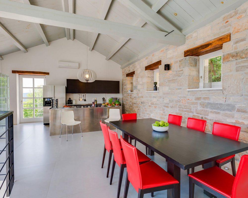Der Essbereich des Ferienhauses ist mit der modernen Küche verbunden.