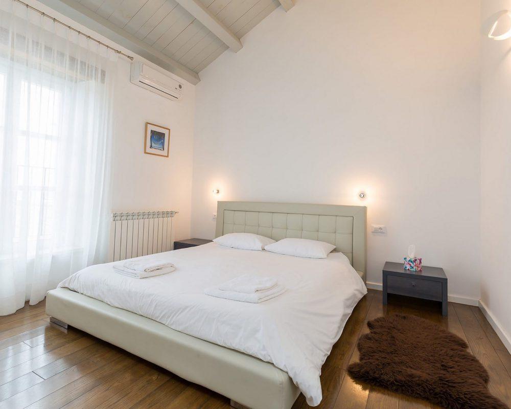Das Doppelzimmer im Obergeschoss besitzt eine Klimaanlage, zwei schicke Nachttische und ein großes Fenster mit toller Aussicht. Ein weicher Fellteppich liegt neben dem Bett.
