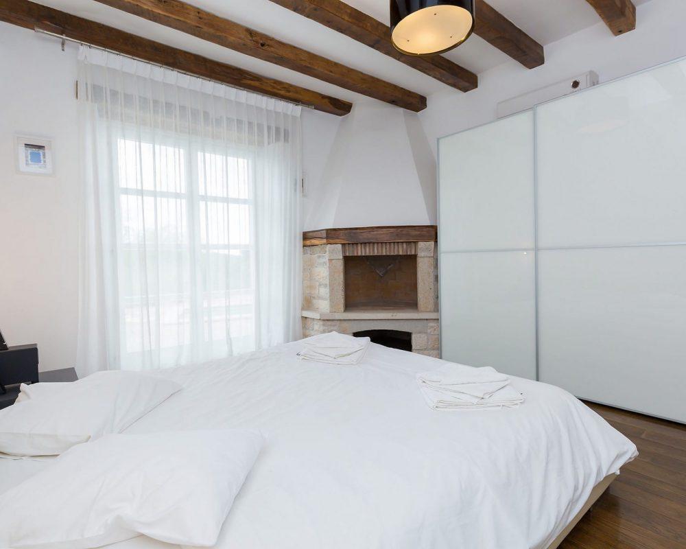 Das große Doppelzimmer im Erdgeschoss besitzt einen offenen Kamin, eine Klimaanlage, einen großen Kleiderschrank mit Schiebetür, sowie einen direkten Zugang zu der Terrasse.