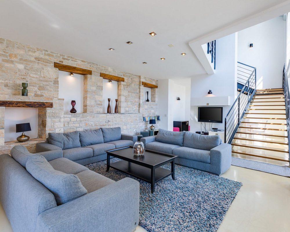 Der Wohnbereich besteht aus einer eleganten Sitzlandschaft mit Teppich und Couchtisch, einem Flachbildfehrnseher und einem offenen Kamin. Eine moderne Treppe führt in das Obergeschoss.