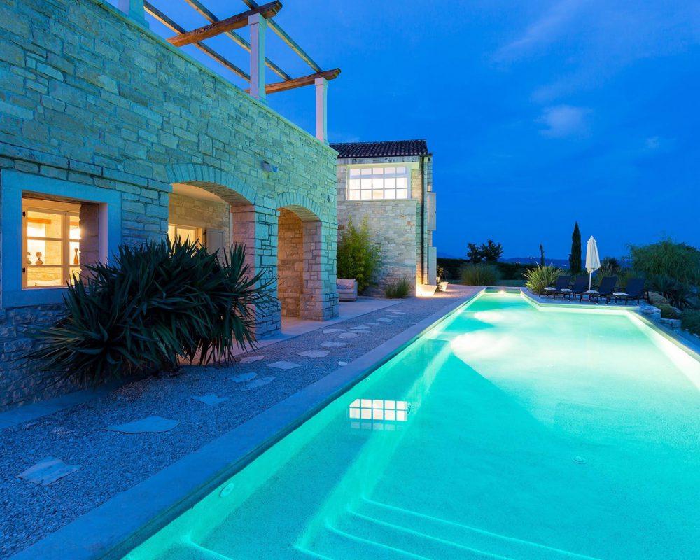 Am Abend wird der Infinity Pool durch Lampen im Wasser erleuchtet. Auch im Außenbereich gehen warme Lichter an.