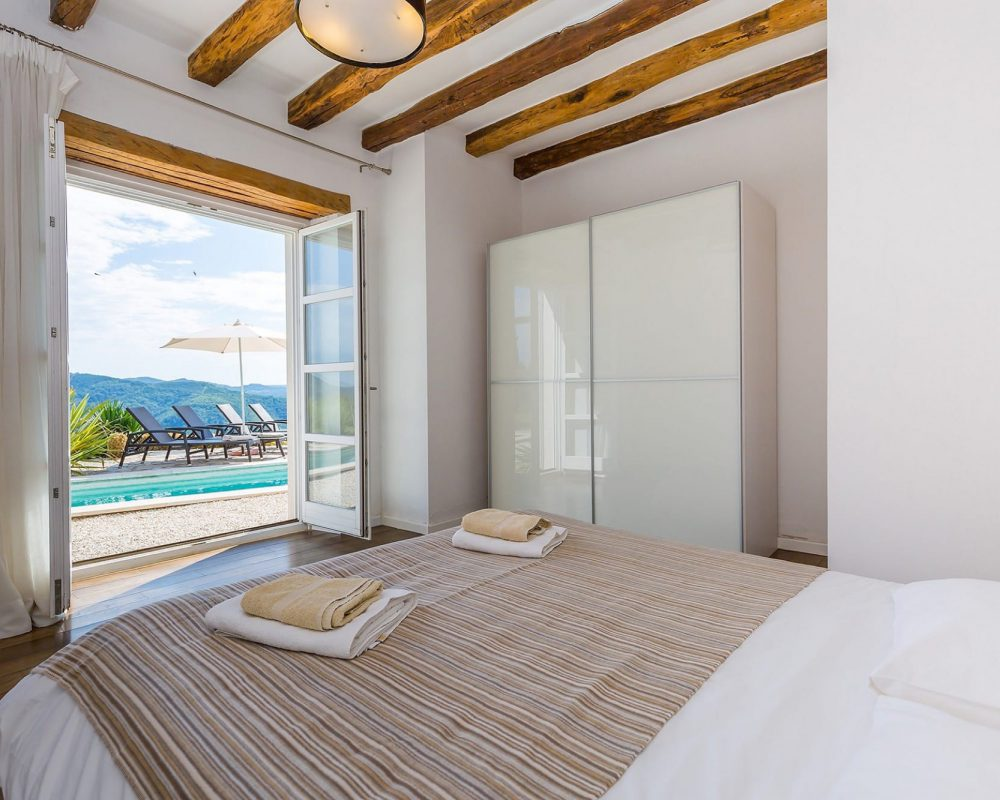 Das dritte große Doppelzimmer im Erdgeschoss hat einen großen Kleiderschrank, eine Klimaanlage und einen Zugang zur Terrasse. Die Tür zur Terrasse führt direkt zum Infinity Pool.