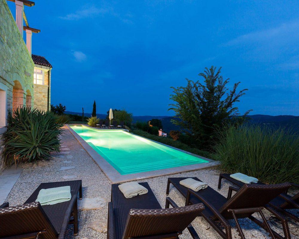 Um den erfrischenden Infinity Pool stehen insgesammt Acht Sonnenliegen. Istrische Pflanzen wachsen auf dem Grundstück der Villa und im dunkeln ist der Außenbereich beleuchtet.