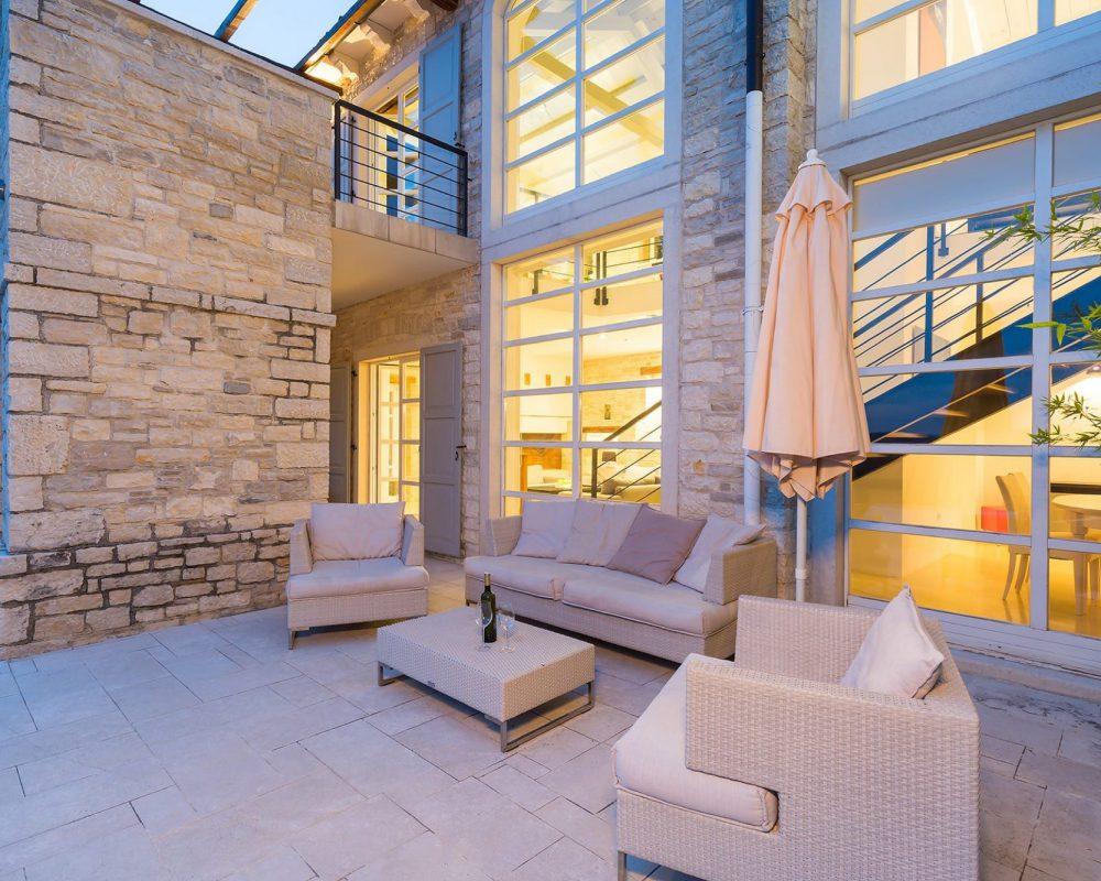 Auf der schicken Terrasse, der Villa Kirin, stehen bequeme Loungemöbel, mit Blick auf den Außenpool.