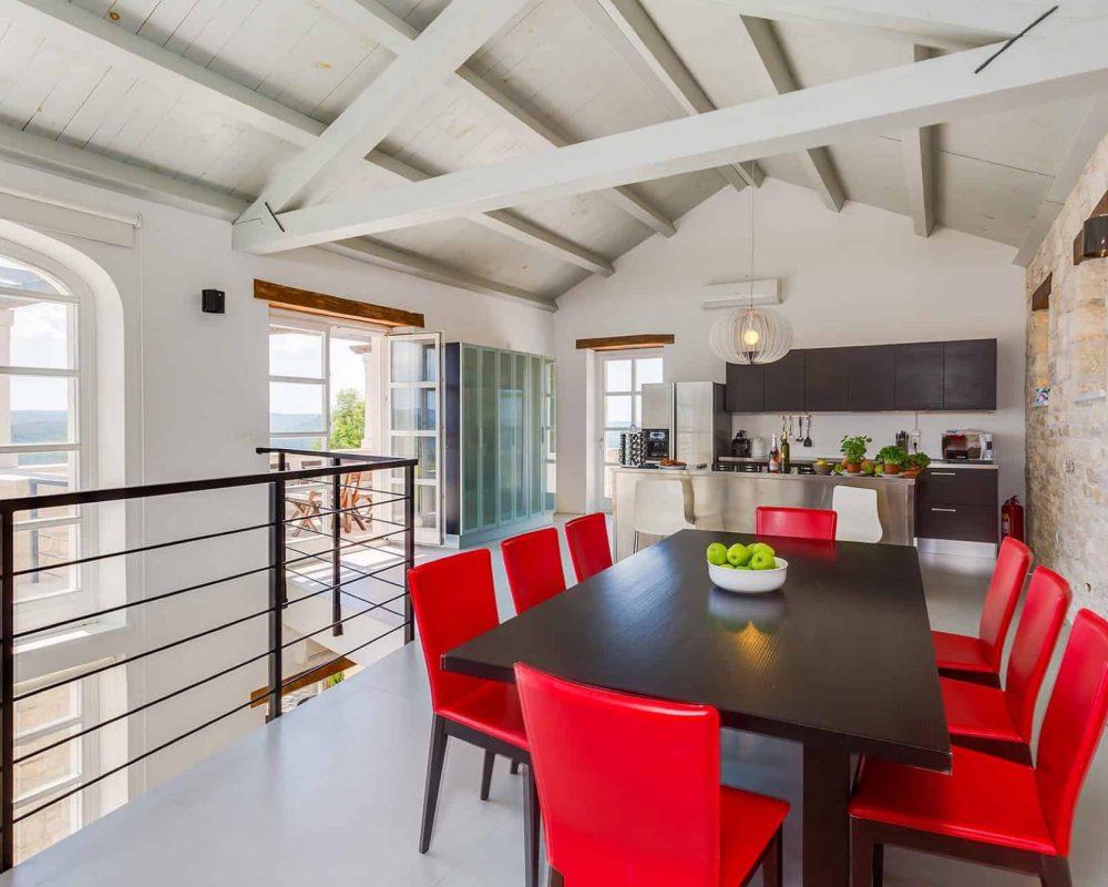 In dem Obergeschoss befindet sich eine offene Küche, ein Essbereich, ein großer Glasschrank und eine schicke Dachterrasse.