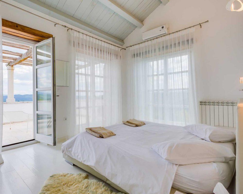 Das schicke Doppelzimmer verfügt über zwei große Fenster und eine eigene Dachterrasse. Eine angebrachte Klimaanlage kühlt den großen Raum.
