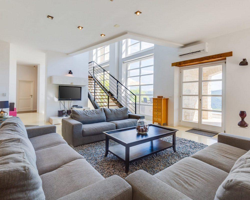 Das Erdgeschoss verfügt über eine Klimaanlage, mehrere Schlafzimmer, einen Flachbildfehrnseher, einen offenen Kamin und eine elegante Sitzlandschaft. Mehrere Türen führen in de Außenbereich.