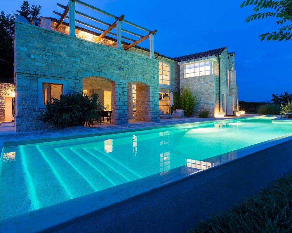 Die Villa Kirin hat drei Terrassen, einen großen Infinity Pool mit Sonnenliegen und einen gepflegten Garten. Am Abend ist das Grundstück schön beleuchtet.