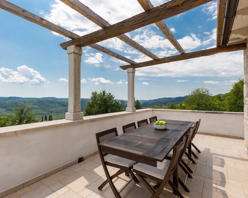 Auf der großen Dachterrase steht ein langer Esstisch mit Acht Stühlen. Sie bietet eine wunderschöne Aussicht auf die Natur.