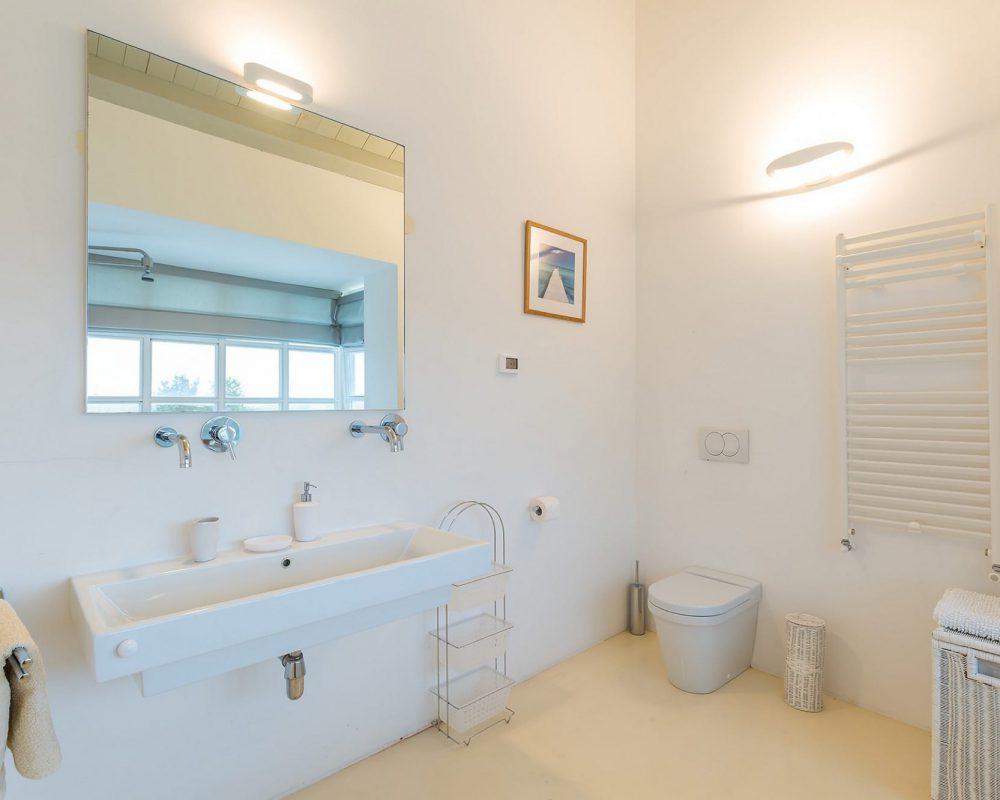 In dem großen Badezimmer im Obergeschoss befindet sich ein langes Waschbecken mit Spiegel, eine Toilette und eine große Badewanne.