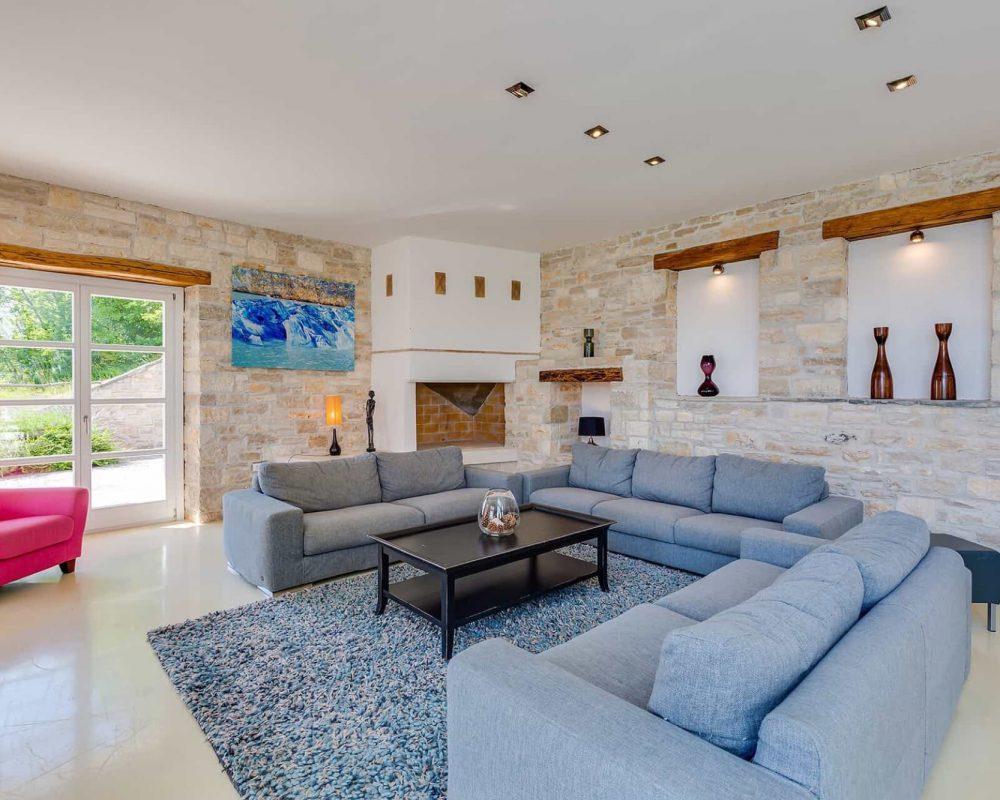 Im Wohnbereich befindet sich eine komfortable Sitzlandschaft mit drei Sofas und einem Sessel. Auch ein offener Kamin und direkte Zugänge auf die Terrasse sind vorhanden.