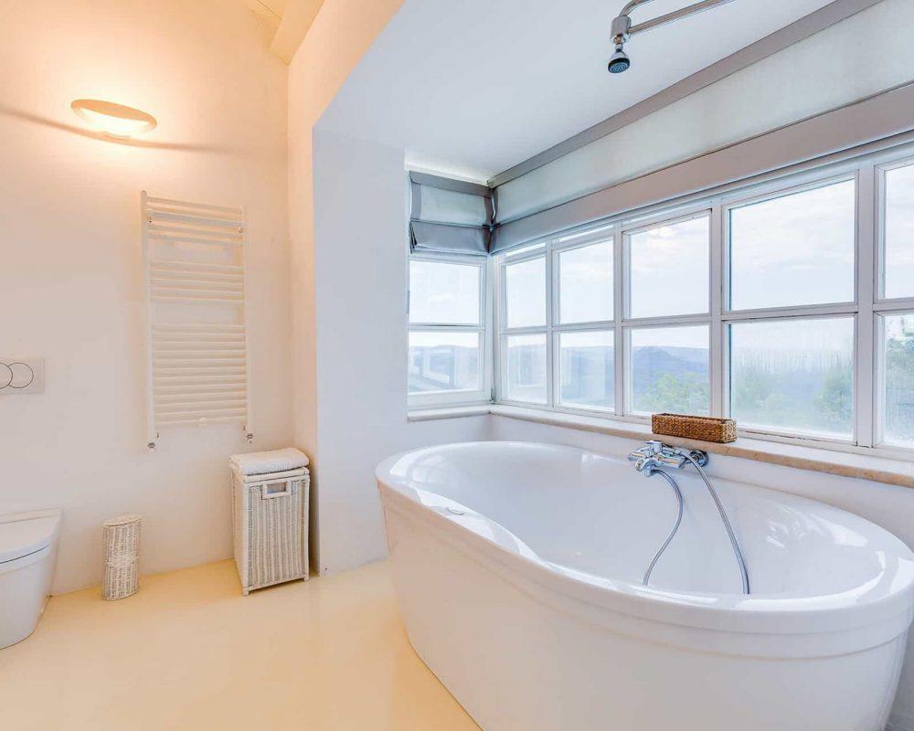 In dem großen Badezimmer befindet sich eine Toilette, ein Wäschekorb und eine elegant geschwungene große Badewanne mit Duschkopf. An den langen Fenstern des Bades sind Fensterabdeckungen als Sonnenschutz.