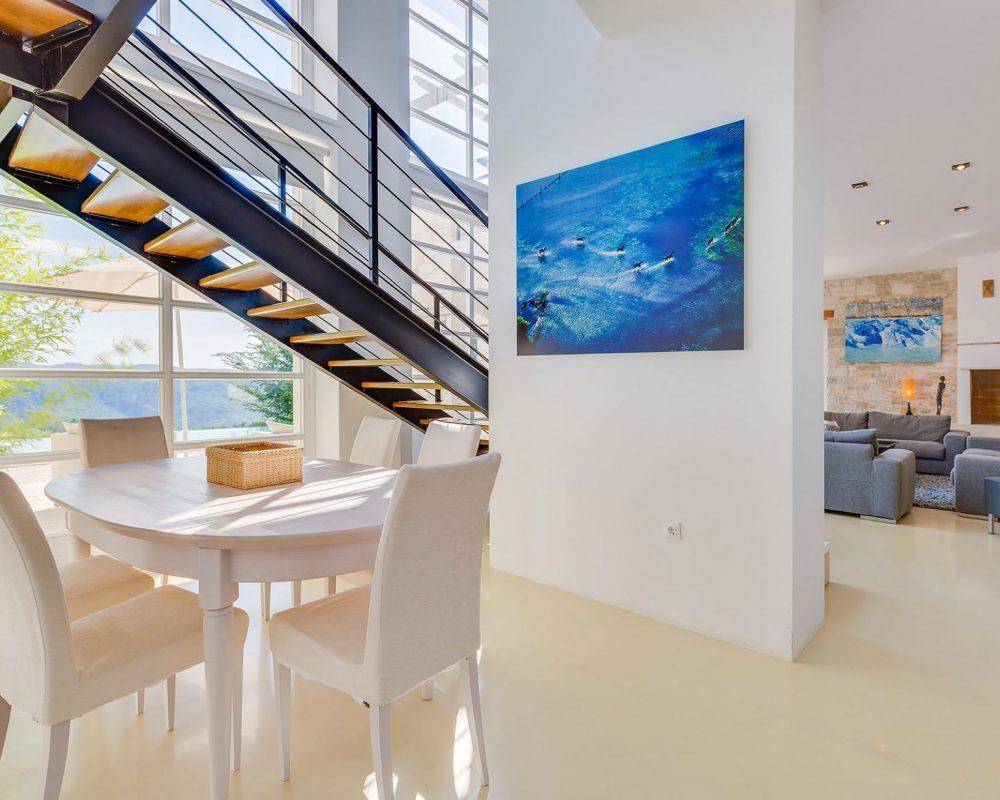 Das Erdgeschoss wird durch die vielen großen Fenster erhellt. Es befindet sich ebenfalls ein eleganter, runder Tisch mit Sechs komfortablen Stühlen und ein schicker Wohnbereich in der unteren Etage.