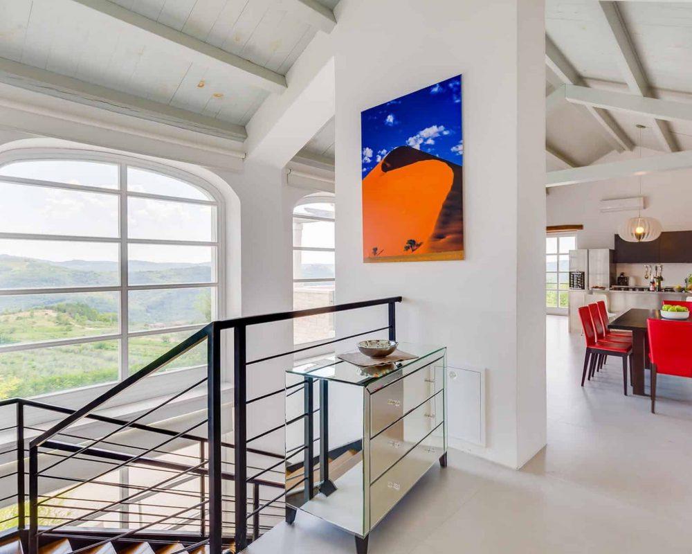 Im Obergeschoss steht ein kleines verspiegeltes Regal neben der Treppe, die in das Erdgeschoss führt. Die Wände der Villa werden mit Bilder dekoriert.