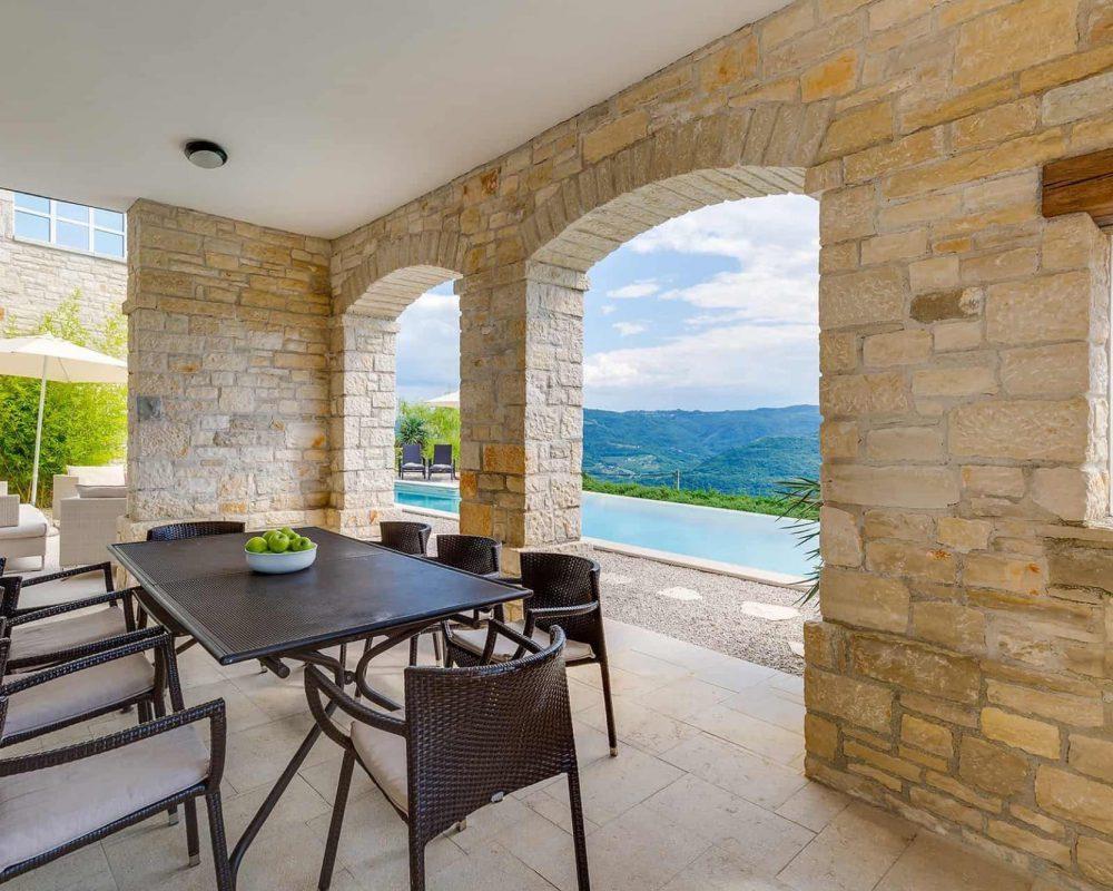Die überdachte Terrasse im Außenbereich bietet einen Esstisch mit Acht Stühlen und einen Außblick auf den gegenüberliegenden Infinity Pool.