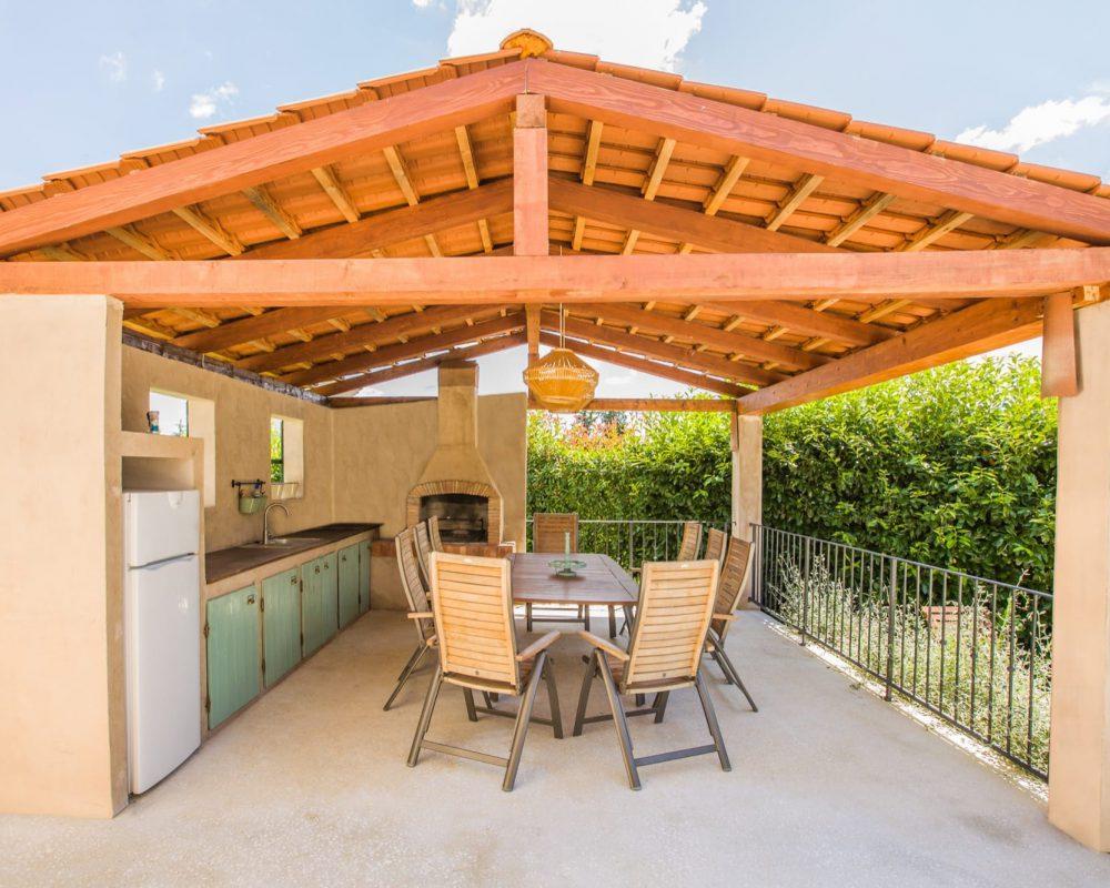 Die rustikale Außenküche ist überdacht und verfügt über einen Grill, einen Kühlschrank und einen Essbereich.
