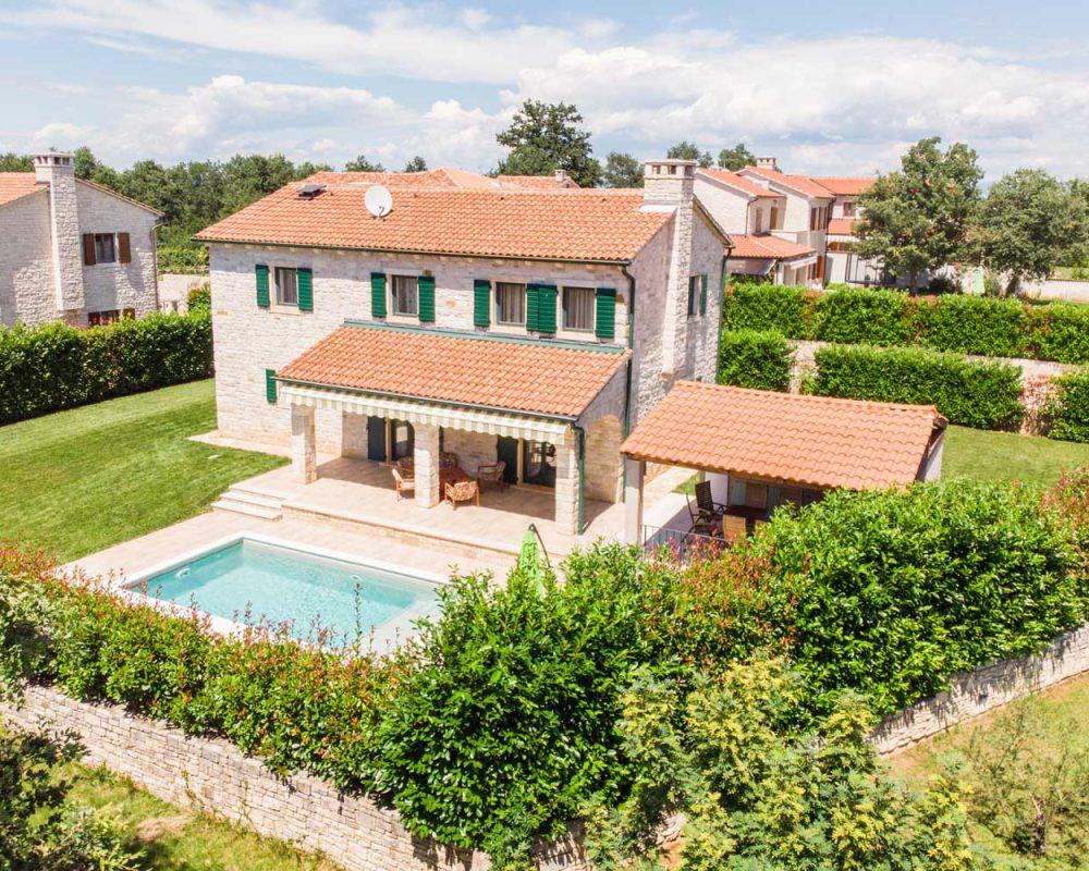 Auf dem Grundstück des Ferienhauses Villa Dracena in Istrien befindet sich ein erfrischender Swimingpool, eine rustikale Außenküche sowie eine überdachte Terrasse mit Loungemöbeln und Markise.