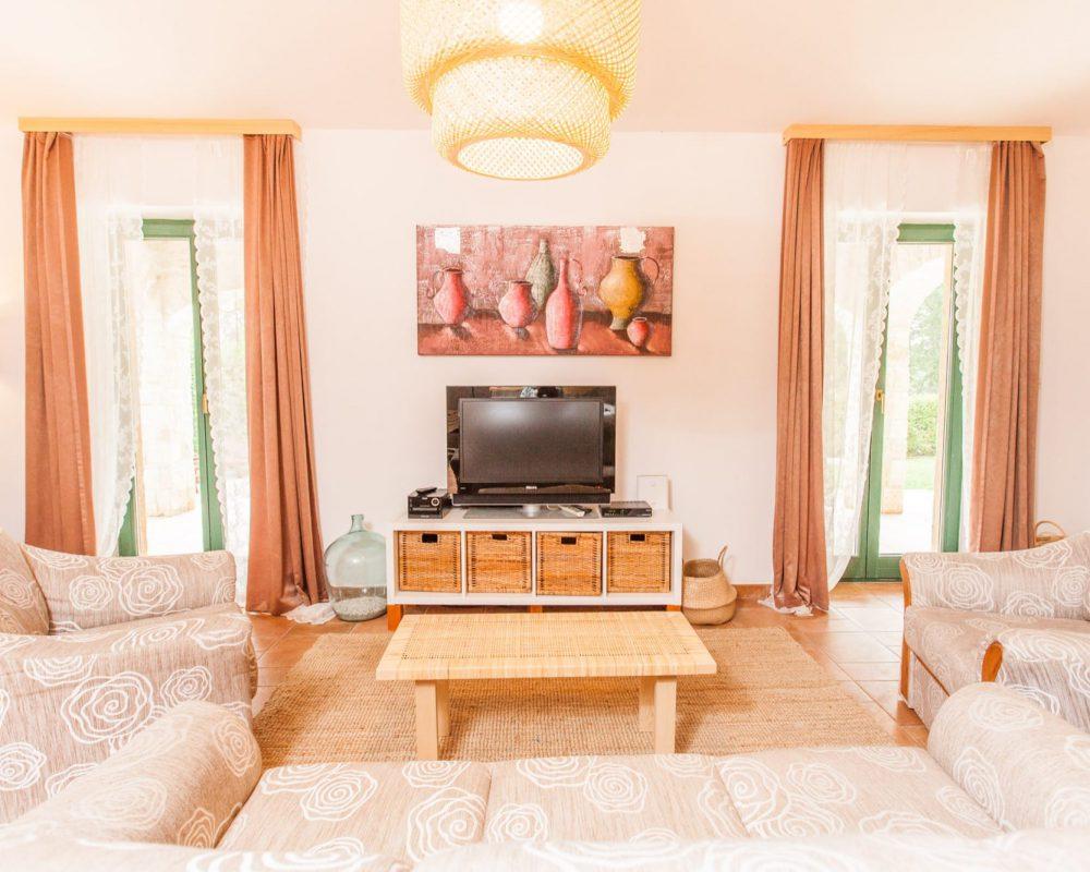 In der Mitte von Couch und Sesseln steht ein kleiner Couchtisch. Gegenüber der Couch steht ein flaches Regal mit einem großen Flachbildfehrnseher.