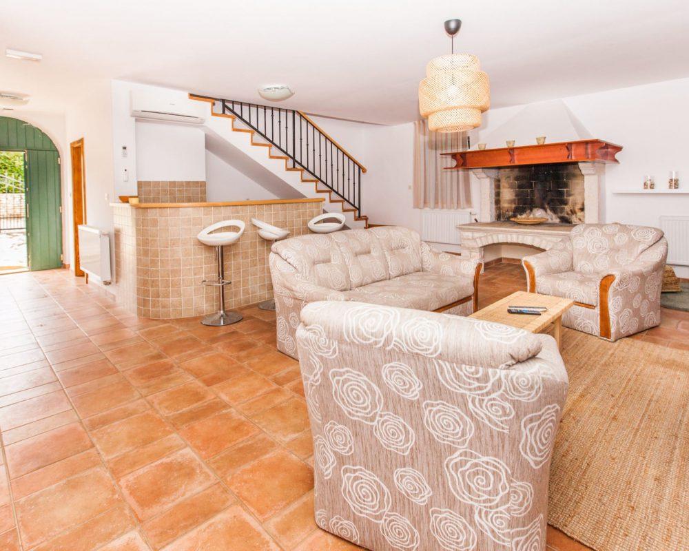 Der große Wohnbereich befindet sich im Erdgeschoss. Er hat ein gemütliches Sofa und zwei Sessel, sowie eine schicke Bar und einen offenen Kamin.