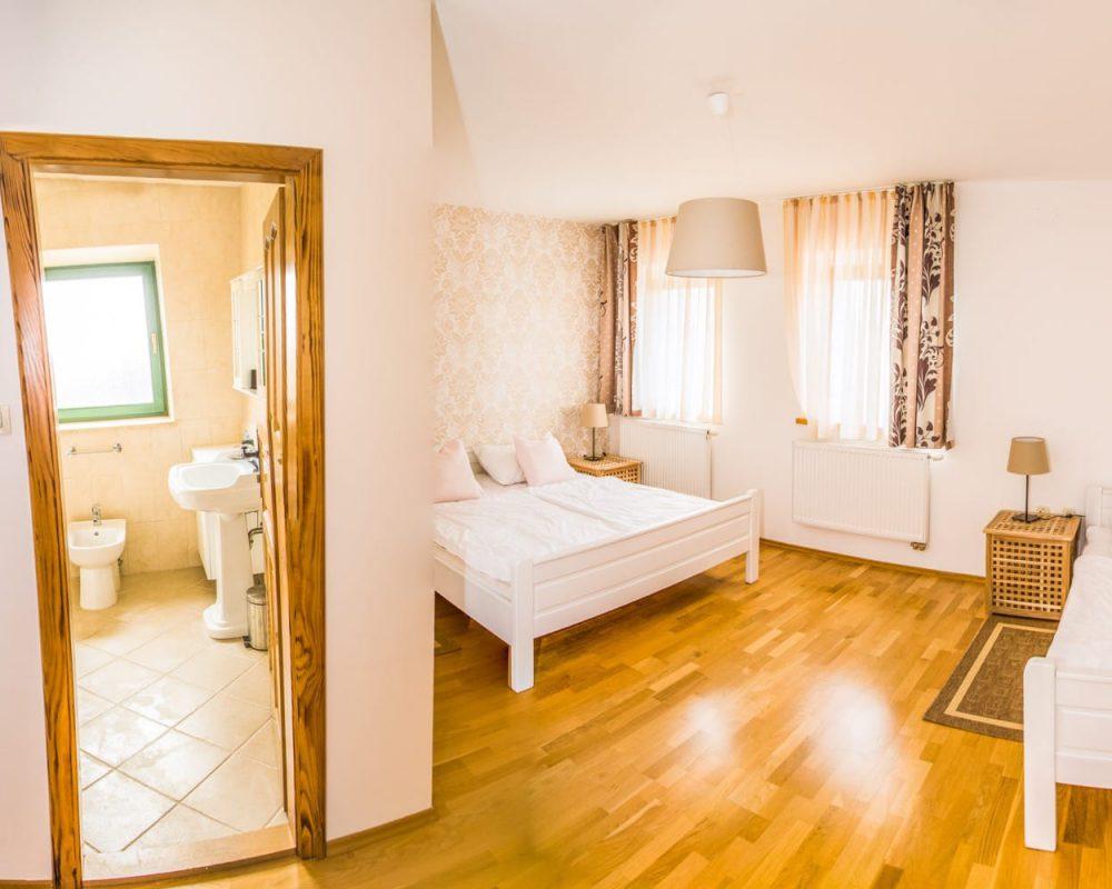 Zu dem großen Dreibettzimmer gehört ein eigenes Bad mit Dusche.