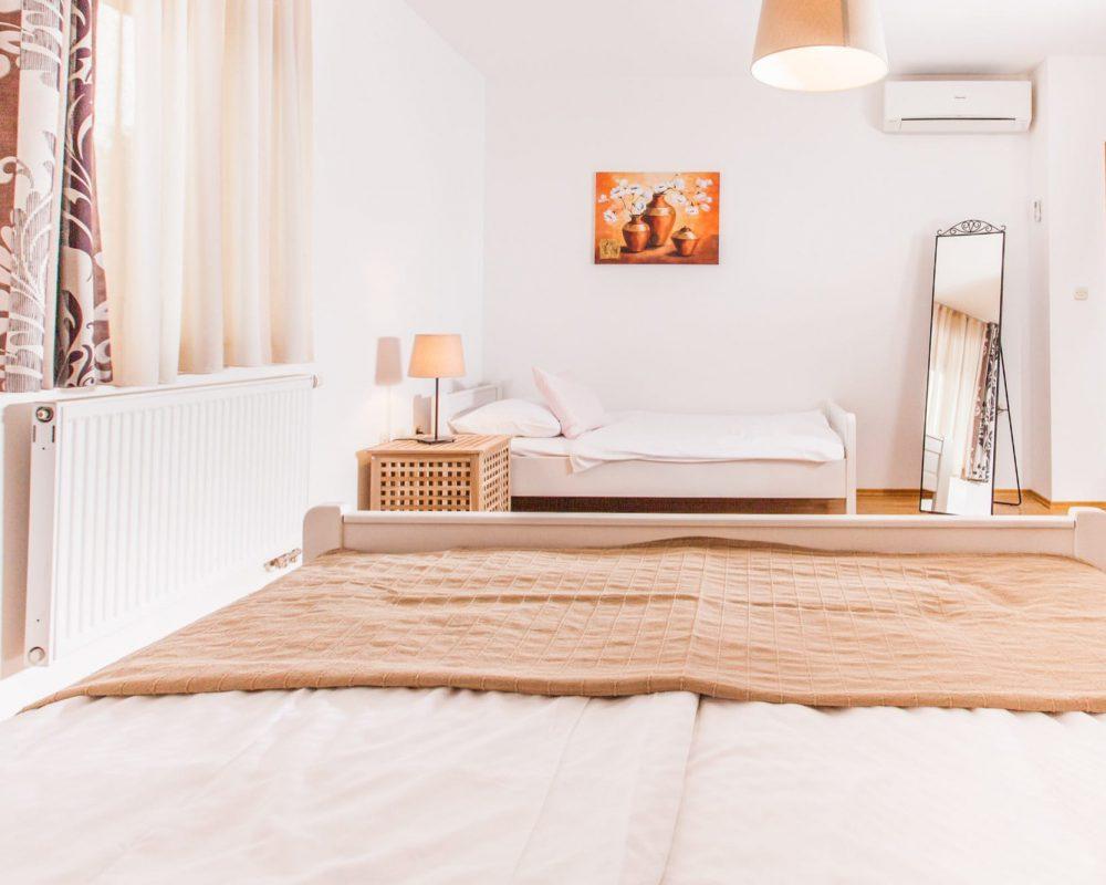 Am der gegenüberliegenden Wand des Doppelbettes steht ein Einzelbett. Neben dem Bett ist ein schicker Standspiegel und eine Klimaanlage.