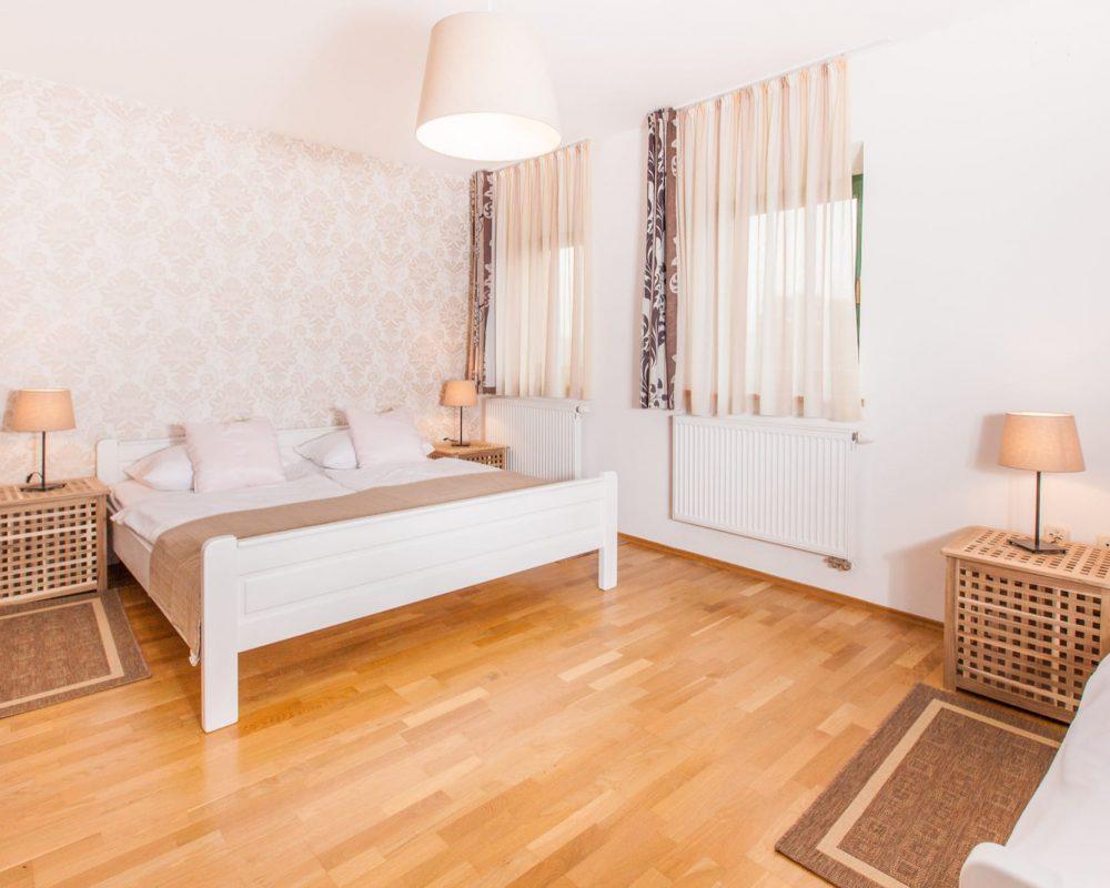 Das große Dreibettzimmer ist hell und freundlich eingerichtet. Das Doppelbett steht gegenüber von dem Einzelbett und hat zwei Nachttische mit Tischlampen neben sich.