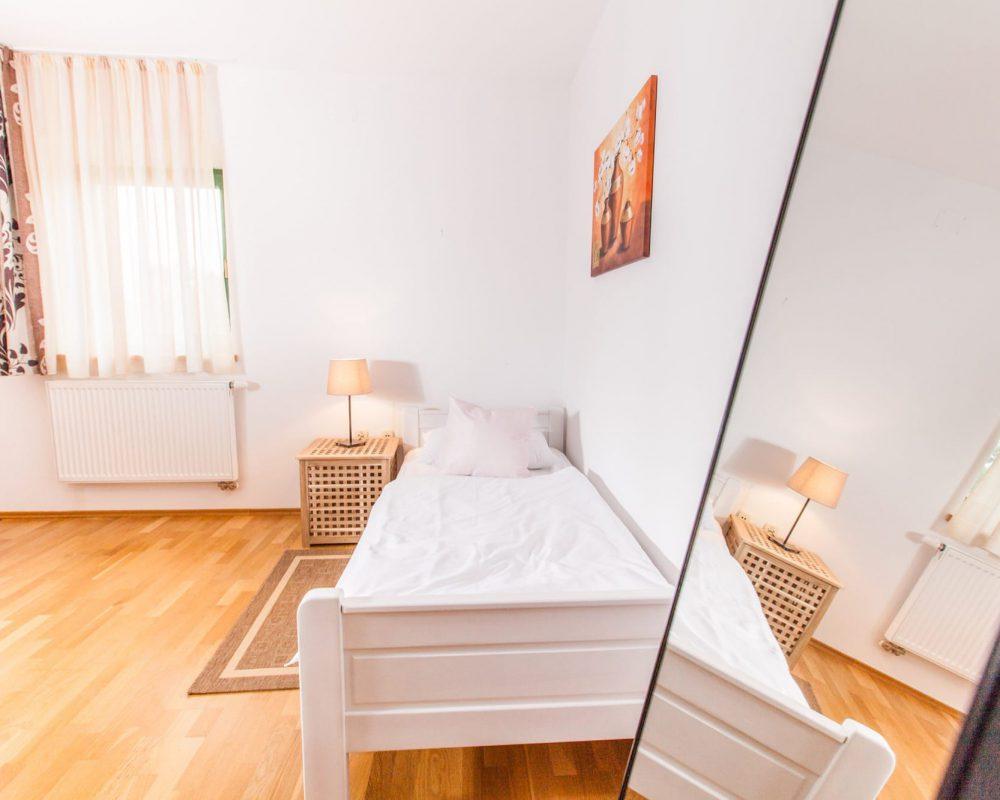 Das komfortable Einzelbett ist im großen Dreibettzimmer. Es hat einen eigenen Nachttisch mit Tischlampe und einen kleinen Teppich.