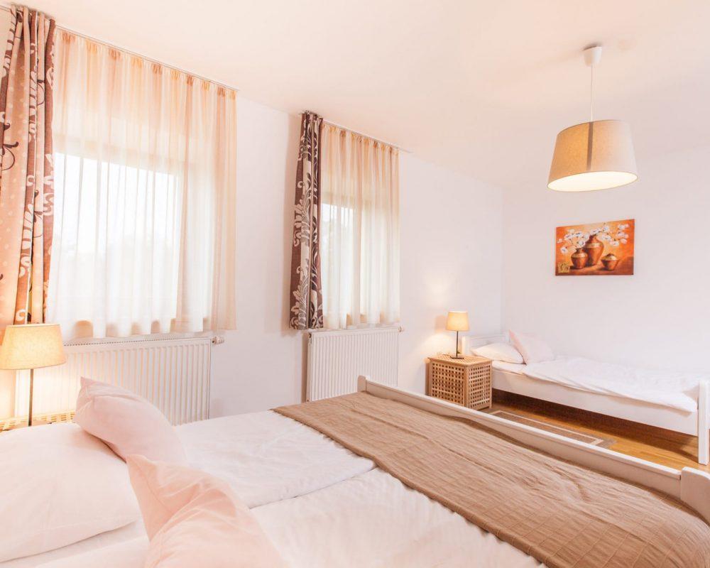 Das große Dreibettzimmer besteht aus drei Betten, drei Nachttischen mit Tischlampen und zwei großen Fenster mit Gardienen.