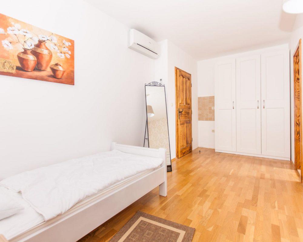 Das große Schlafzimmer hat drei gemütliche Betten, eine Klimaanlage, einen großen Kleiderschrank und einen schicken Standspiegel.