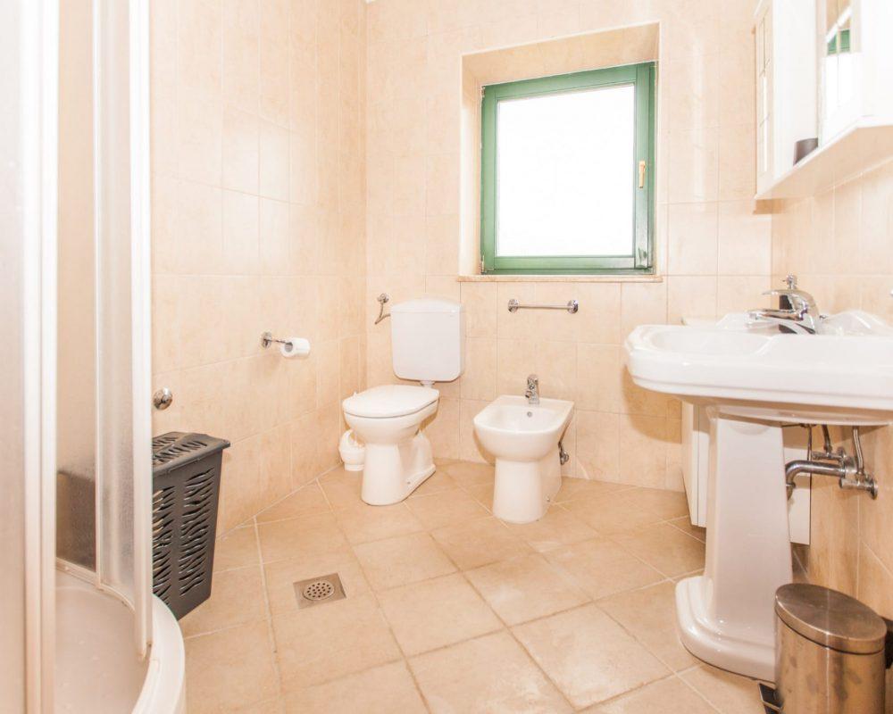 Das Badezimmer in der ersten Etage hat einen Badschrank mit Spiegeln und eine Dusche mit Schiebetüren.