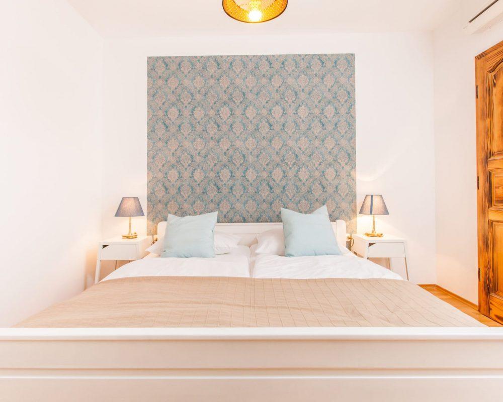 In dem Doppelzimmer gibt es eine Klimaanlage und zwei schicke Nachtschränke mit Tischlampen.