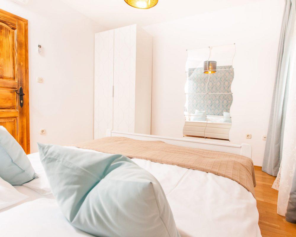 Gegenüber von dem Doppelbett ist ein geschwungener, langer Spiegel und ein hoher Kleiderschrank.
