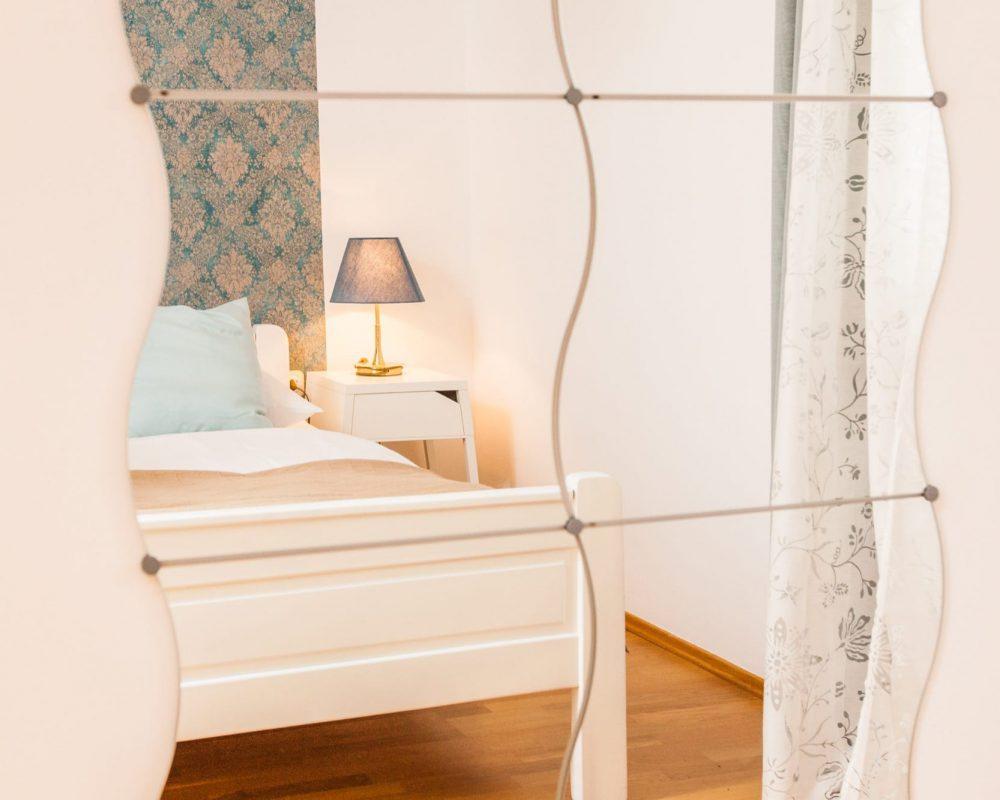 Der lange, geschwungene Spiegel ist genau gegenüber von dem Doppelbett.