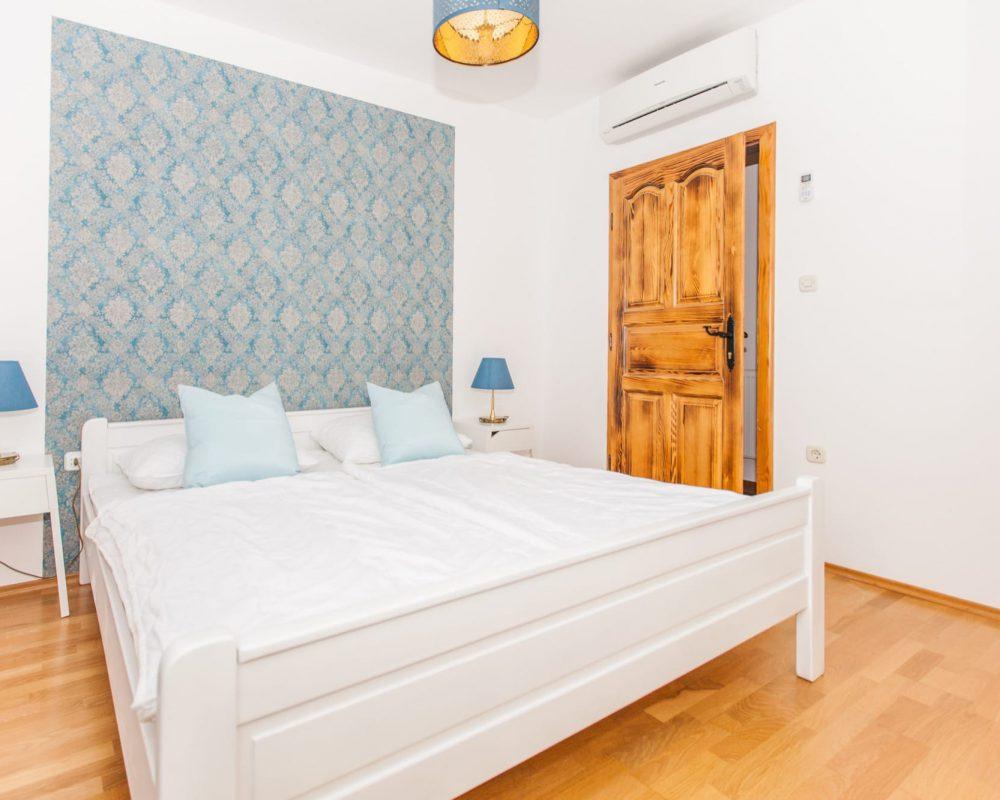 Das blau,- weiße Doppelzimmer ist schick und modern eingerichtet. Es hat eine Klimaanlage und zwei Nachttische mit Tischlampen.
