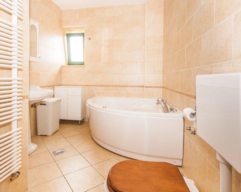 In dem großen Badezimmer steht ein kleiner quadratischer Badschrank, eine Dusche und eine große Eckbadewanne.