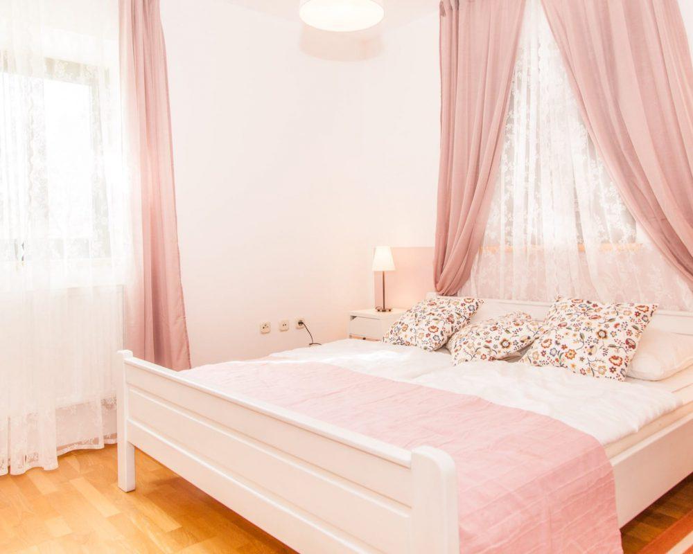 Das romantische Doppelzimmer hat zwei Fenster mit schicken Gardienen.