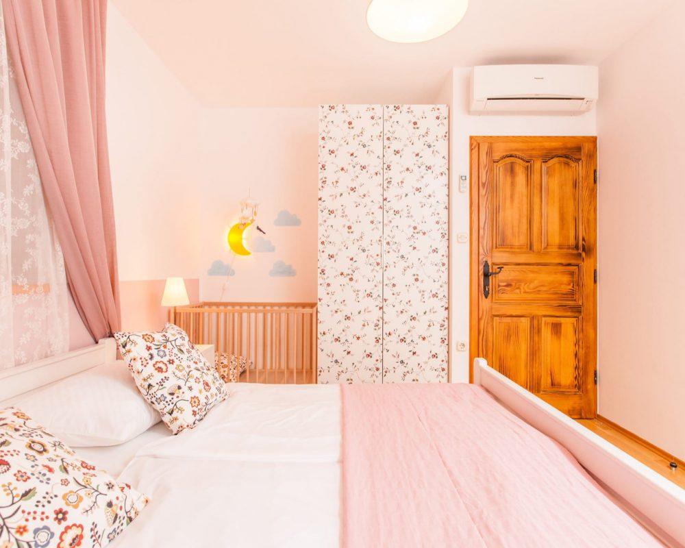 In dem romantischen Doppelzimmer ist eine Klimaanlage, ein hoher Kleiderschrank und ein Gitterbett aus Holz mit einem Baby Mobile.