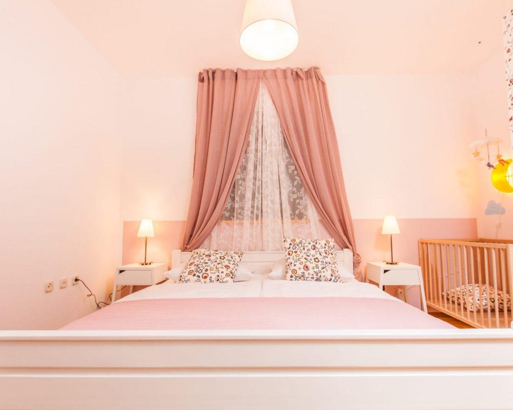 Das romantisch eingerichtete Doppelzimmer hat zwei Nachttische mit Nachlleuchten und ein hohes Fenster, direkt über dem Bett.