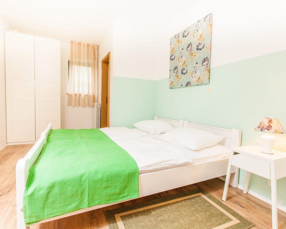 In dem großen Schlafzimmer mit eigenem Bad befindet sich außerdem ein hoher Kleiderschrank. Mehrere Fenster und ein Nachtlicht auf einem Nachttisch erhellen den Raum.