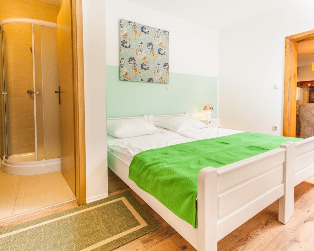 Zu dem großen Doppelzimmer gehört ein eigenes Bad mit Dusche und ein direkter Zugang in den Wohnbereich.