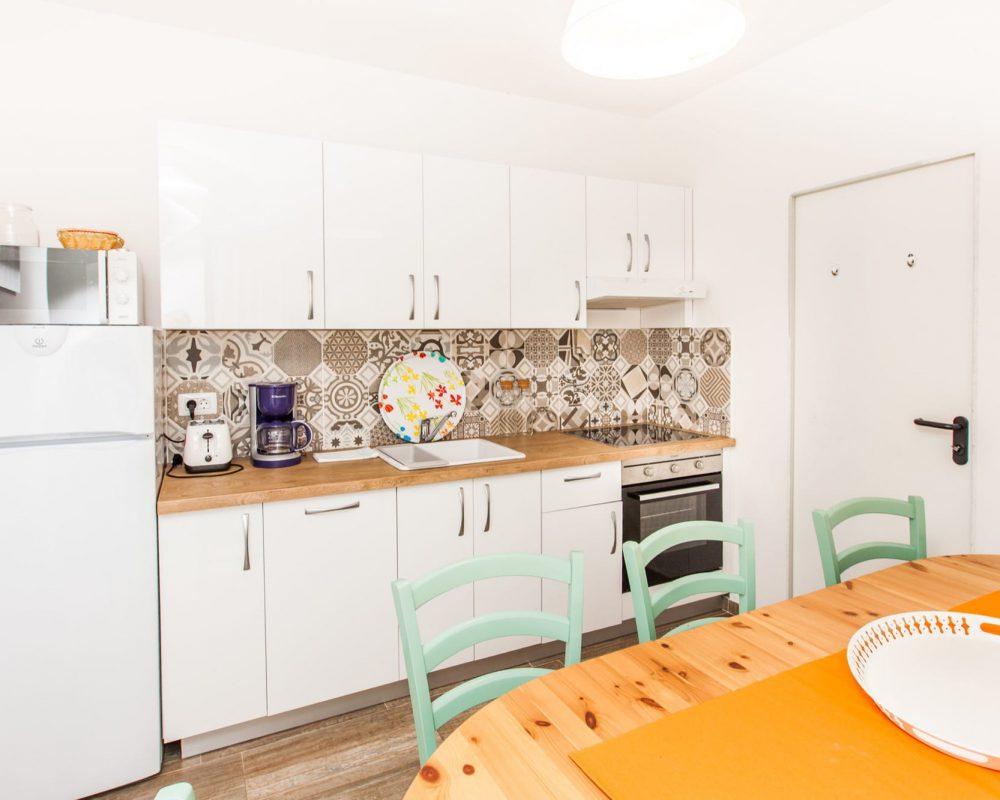 Die moderne, vollausgestattete Küche hat einen Essbreich mit Sieben Stühlen. Sie verfügt über enen großen Kühlschrank, inen Ofen und einen Herd mit Abzug.