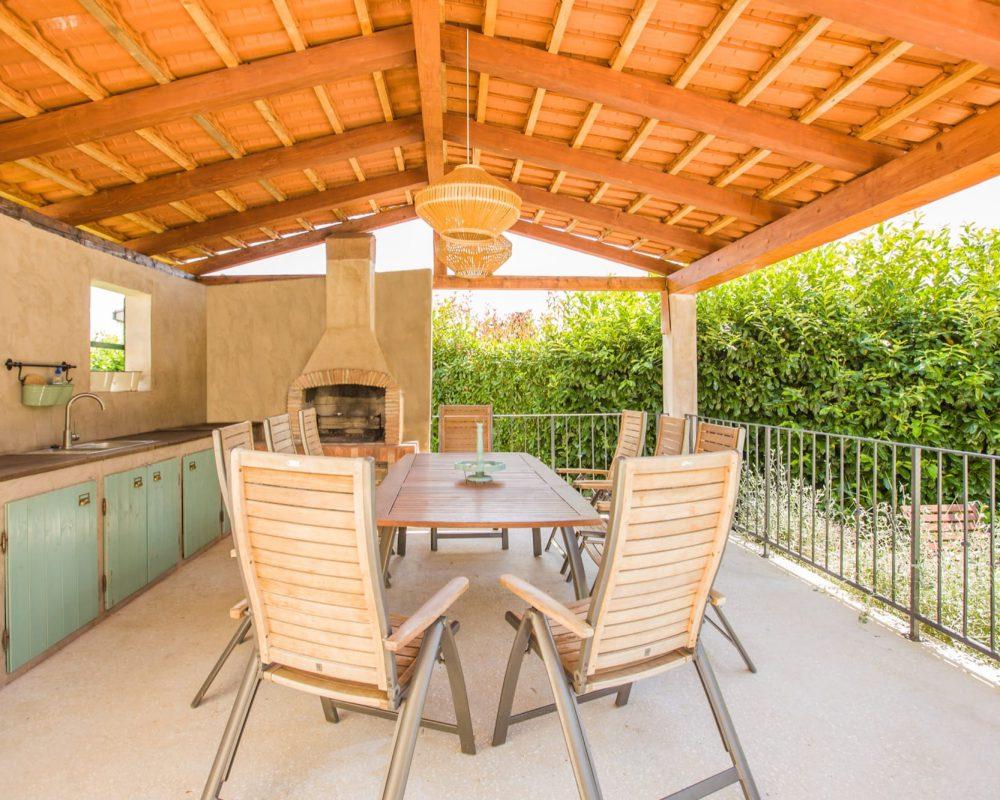 Die rustikale Außenküche verfügt über einen Grill und einen überdachten Essbereich.