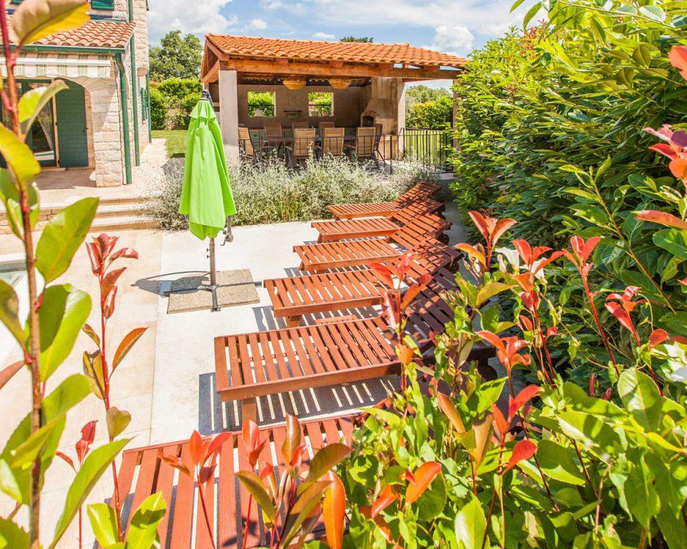 Auf der großen Terrasse der Villa Dracena stehen sechs schicke Sonnenliegen mit Blick auf den erfrischenden Swimmingpool.