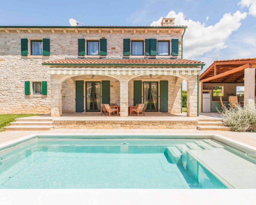 Gegenüber des Swimmingool ist die überdachte Terrasse mit bequemen Loungemöbeln. Von der Terrasse führe zwei große Türen direkt in die Villa.